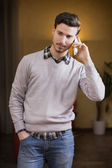 Handsome young man talking on the phone at home — Stock fotografie