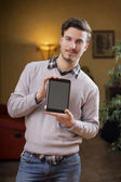 Handsome young man at home with tablet PC in his hands — Stock Photo