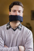 Gagged young man cannot speak — Stock Photo