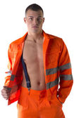 Young construction worker with orange suit open on naked torso — Stock Photo