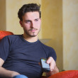Handsome young man on counch, using TV remote control — Stock Photo