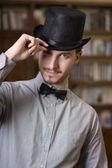 Aantrekkelijke jonge man dragen hoge hoed en strikje — Stockfoto