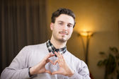 Handsome young man making heart sign with hands — Stock Photo
