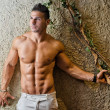 Muscular young latino man shirtless in white pants leaning on wall — Stock Photo