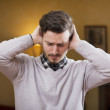 Handsome young man covering his ears, too much noise — Stock Photo #41597641