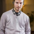 Attractive young man listening to music on headphones at home — Stock Photo