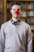 Handsome young man smiling with red clown nose — Stock Photo