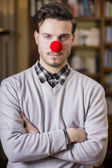 Serious young man with red clown nose — Stock Photo