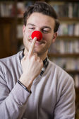 Handsome young man smiling and touching red clown nose — Photo