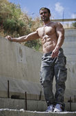 Muscle man shirtless outdoors leaning against concrete wal — Stock Photo