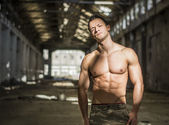 Muscular shirtless young man in abandoned warehouse standing — Stock Photo
