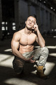 Muscular shirtless young man in abandoned warehouse kneeling — Stock Photo
