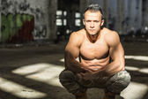 Muscular shirtless young man in abandoned warehouse sitting — Stock Photo