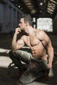 Profile of muscular shirtless young man in abandoned warehouse — Stock Photo