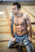 Muscular shirtless young man with denim overalls kneeling — Stock Photo