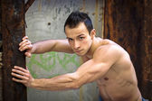 Muscular young man standing, leaning against rusty metal structure — Stock Photo