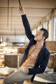 Muscular young man in messy workplace, hanging from tube — Stock Photo