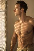 Muscular shirtless man lit by sun behind venetian blinds — Stock Photo
