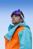 Friendly attractive skier or snowboarder against blue sky — ストック写真