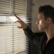 Profile of young man peeking through venetian blinds — Stock Photo