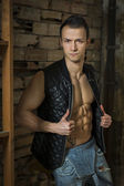 Muscular shirtless young man with jeans and sleeveless jacket — Stock Photo