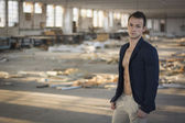 Muscular young man in empty abandoned workplace — Stock Photo