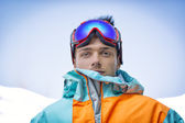 Friendly attractive skier or snowboarder against blue sky — Stock Photo