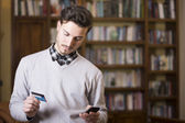 Handsome young man shopping online on mobile phone — Stock Photo
