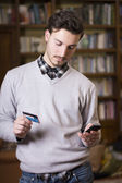 Attractive young man shopping online on mobile phone — Stock Photo