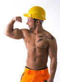 Muscular young construction worker shirtless looking at his bulging bicep — Stock Photo