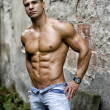 Muscular young latino man shirtless in jeans in front of concrete wall — Stock Photo #45679013
