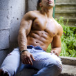 Muscular young latino man shirtless in jeans sitting against concrete wall — Stock Photo