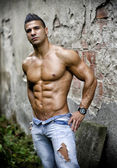 Muscular young latino man shirtless in jeans in front of concrete wall — Stock Photo