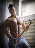 Muscular shirtless young man with farming tool — Stock Photo