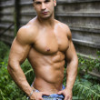 Muscular young latino man shirtless in jeans in front of concrete wall — Stock Photo #45704151