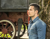 Profile of young man in denim shirt near old train, against tree — Stock Photo