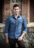 Handsome young man with denim shirt standing outdoors, smiling — Stock Photo
