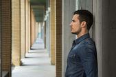 Attractive young man in narrow columns corridor outdoors — Stock Photo