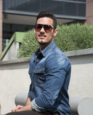 Handsome young man with denim shirt and sunglasses  — Stock Photo