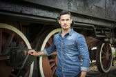 Handsome young man in denim shirt in front of old train — Stock Photo