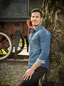 Smiling young man in denim shirt against tree near old train — Stock Photo