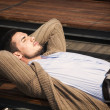 Attractive young man laying down on wood bench — Stock Photo