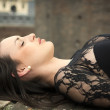 Pretty brunette young woman lying down on brick wall — Stock Photo