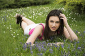 Attractive young woman laying down in grassland, casual dress — Stock Photo