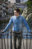Young man wearing denim shirt on city bridge in Treviso, Italy — Stock Photo