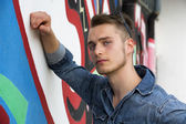 Handsome blond young man against colorful graffiti wall — Stock Photo