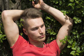 Attractive young blond man against wall of green ivy — Stok fotoğraf