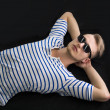 Cool blond young man laying on the floor with sunglasses on — Stock Photo #48965645