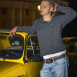 Night shot of young man standing next to small car — Stock Photo #48966587
