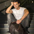 Handsome young man sitting on stairs' granite steps — 图库照片
